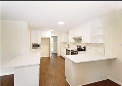 Hallie Brown Builders White cabinets over hardwood flooring